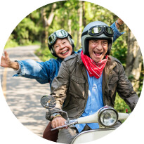 An older man and woman on a motorcycle, smiling and having fun