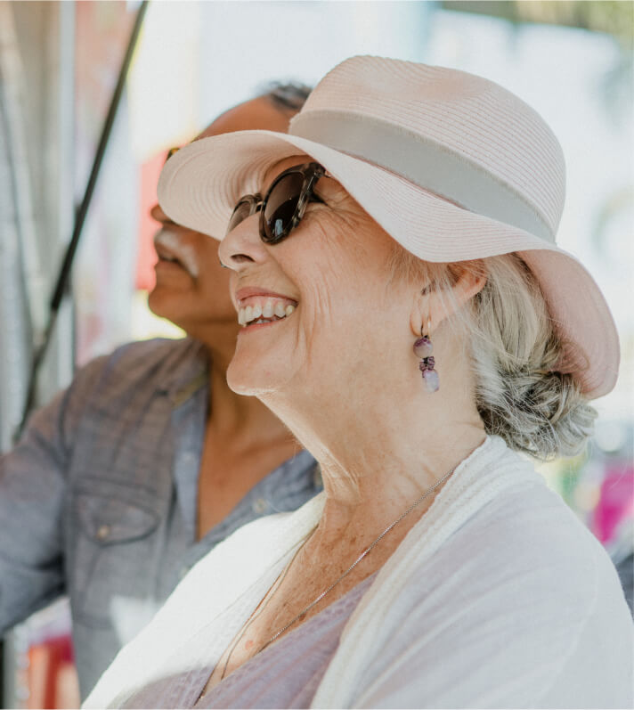 An older woman with a pink hat and dark sunglasses, smiling